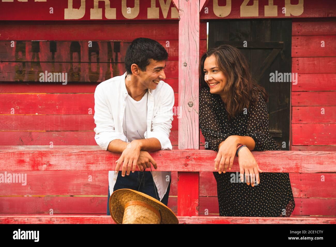Hübsches Paar Flirten und lächeln sich gegenseitig außerhalb eines roten Holzsalons. Ranch Konzept Fotografie Stockfoto