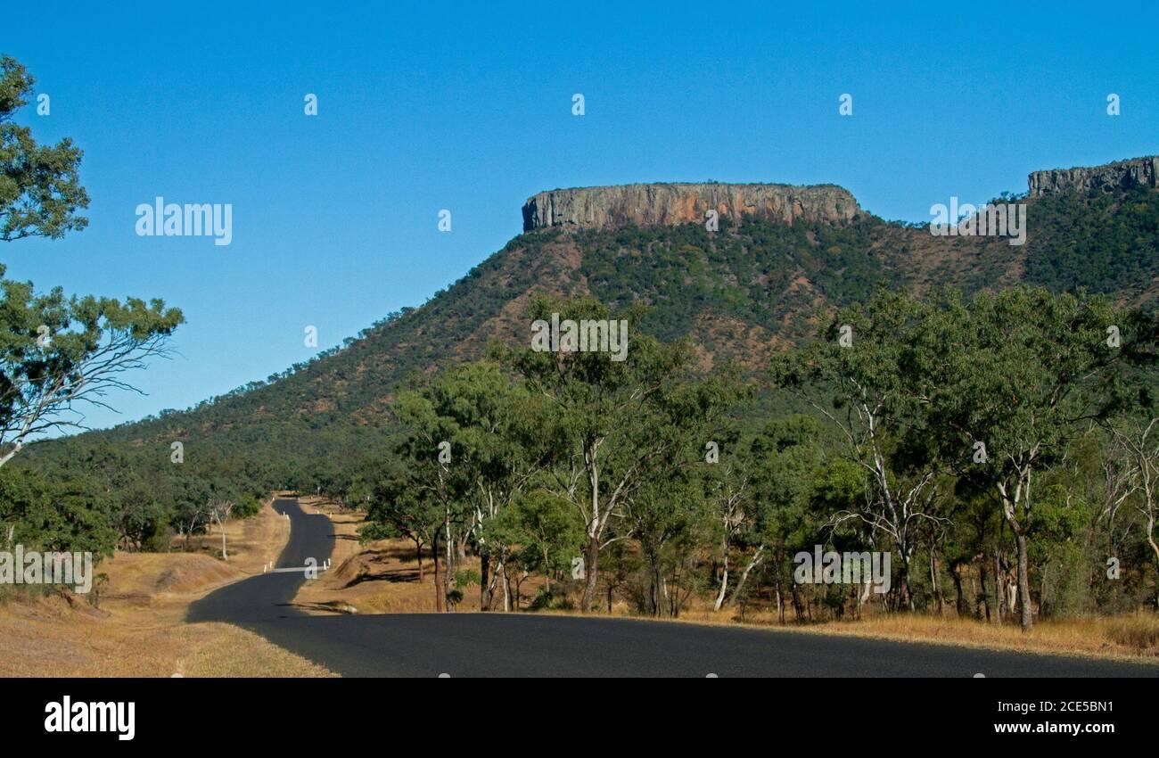 Lords Tafelberg im Peak Range National Park steigt in Blauer Himmel mit Straße, die durch den Vordergrund schlängelt, bedeckt von Bäumen Im Outback Australien Stockfoto