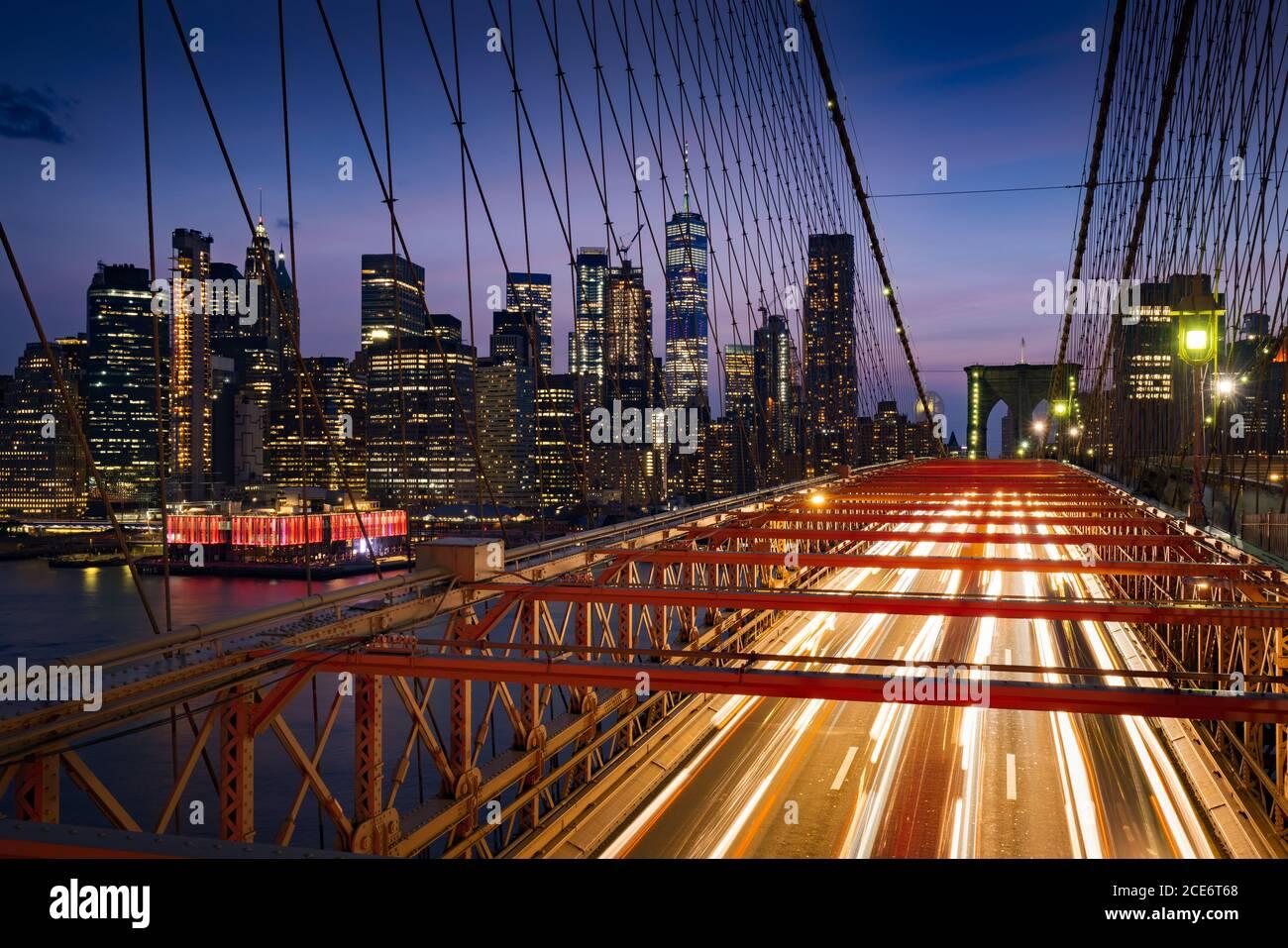 Wolkenkratzer in Lower Manhattan bei Dusk und Brooklyn Bridge mit leichten Pfaden. Abend in New York City, NY, USA Stockfoto