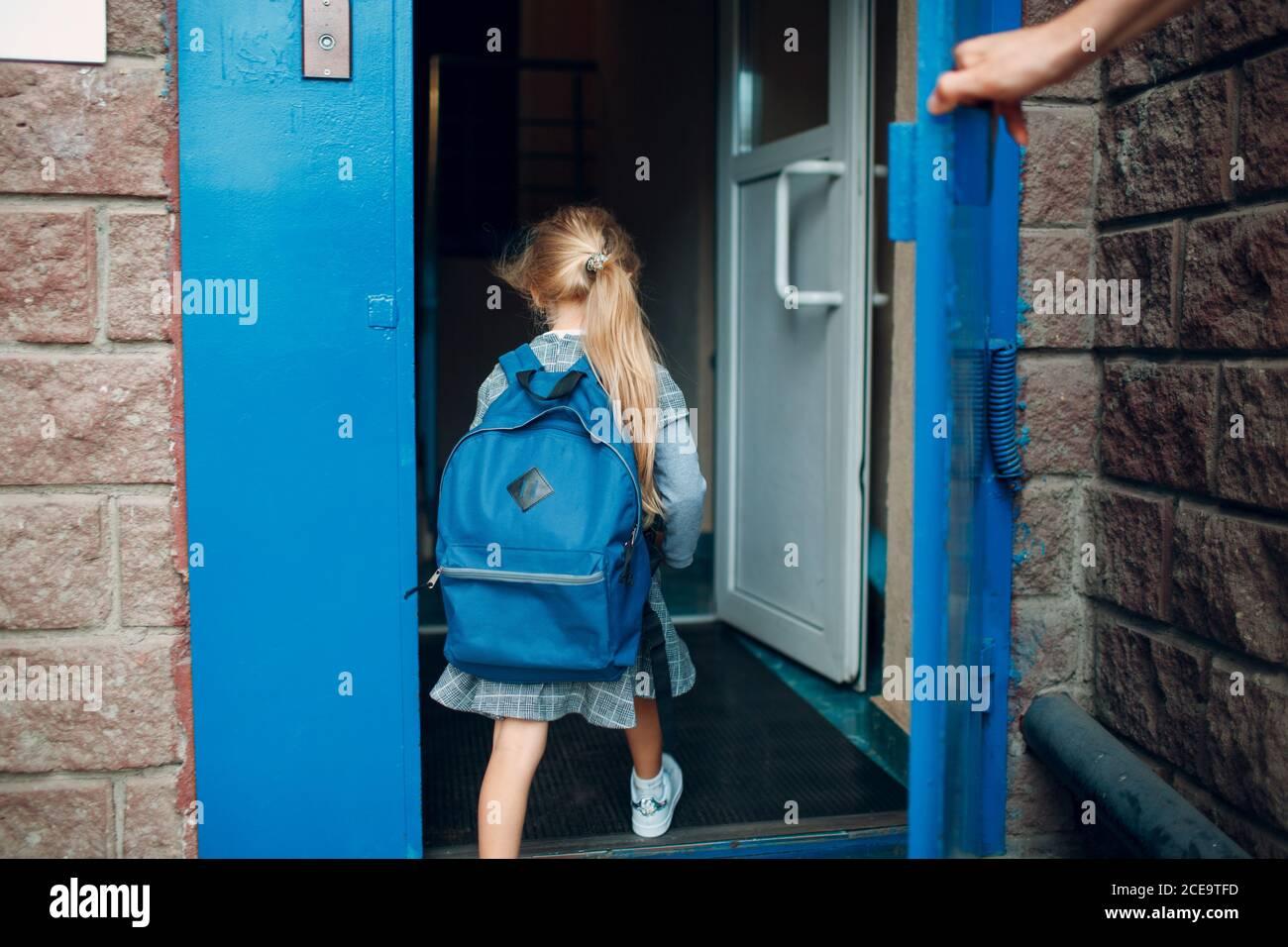 Rückansicht des Vaters, der von der Schule nach Hause kommt Mit seiner Tochter, die Rucksack trägt Stockfoto