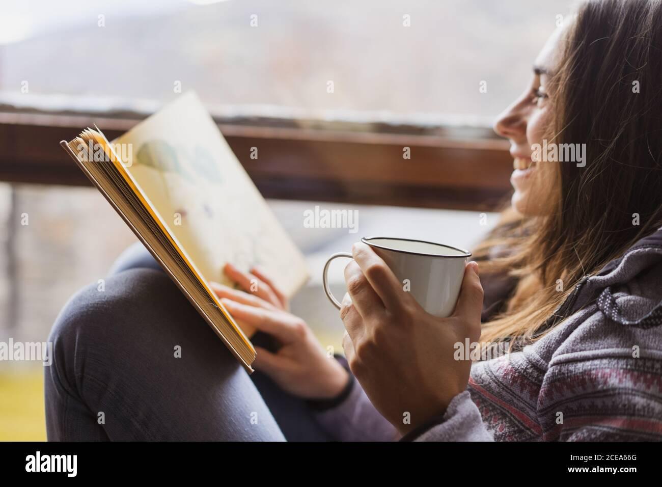 Seitenansicht der jungen Dame mit Tasse frisch heiß Trinken Sie beim Lesen des interessanten Buches, während Sie neben dem riesigen Fenster sitzen Gemütliches Zimmer Stockfoto