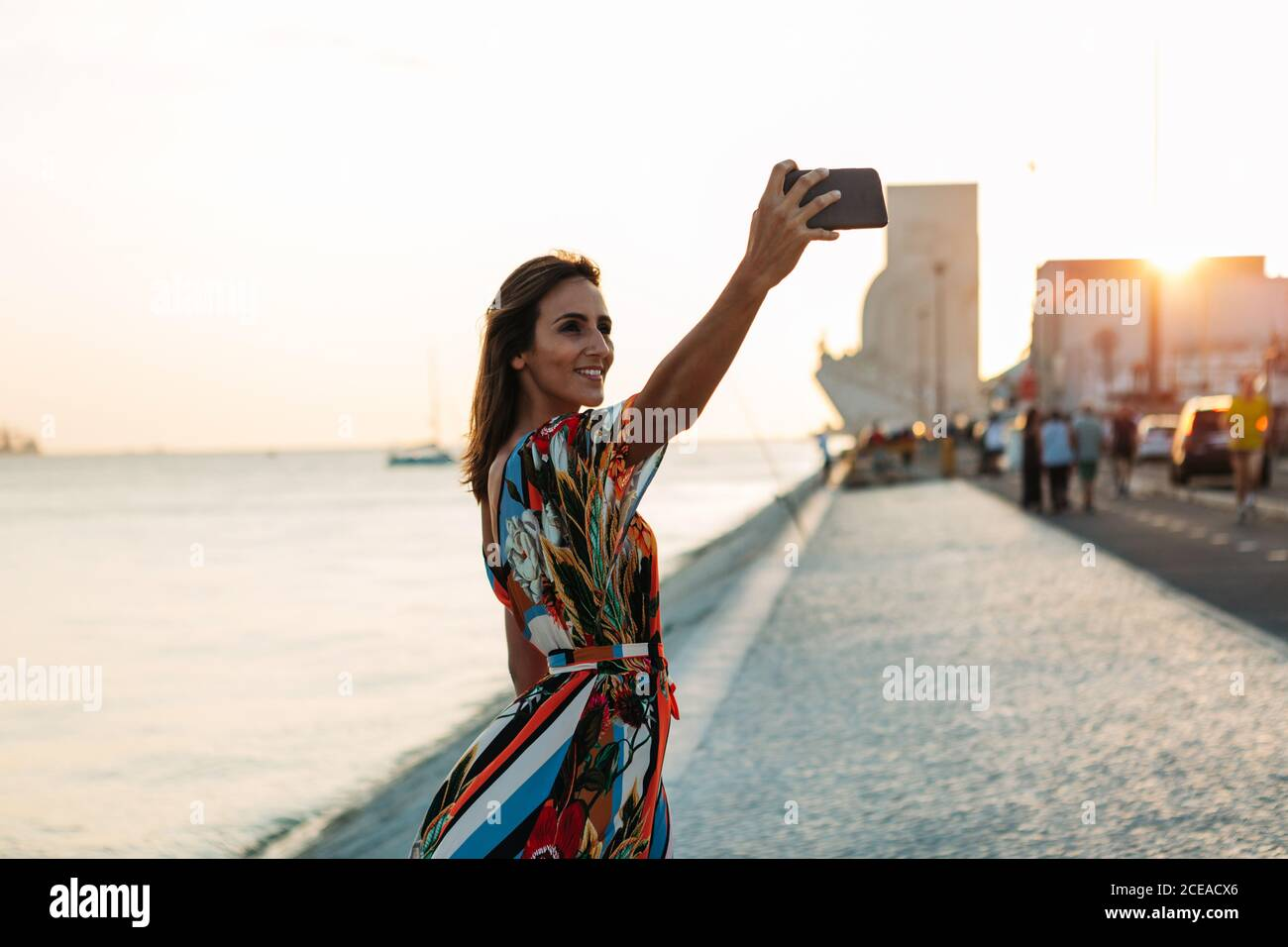 Content Frau in Kleid mit Telefon und Selfie auf Strandpromenade bei Sonnenuntergang Stockfoto