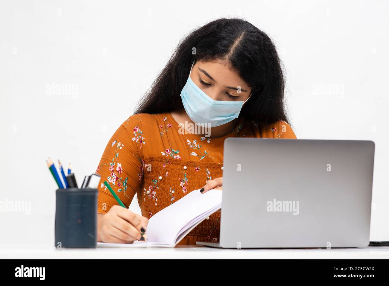 Hübsche junge indische Frau sitzt vor weißem Hintergrund und mit ihrem Laptop. Nette Teenager tun ihre Online-Schularbeiten von zu Hause aus Stockfoto