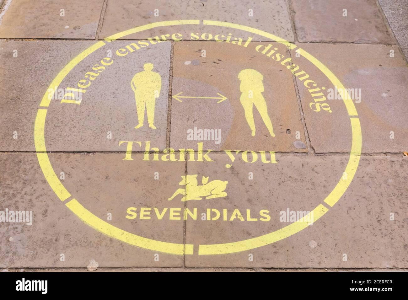 Soziale Distanzierung in Covent Garden, London, England, Zeichen und Ratschläge zu Regeln auf dem Bürgersteig Stockfoto