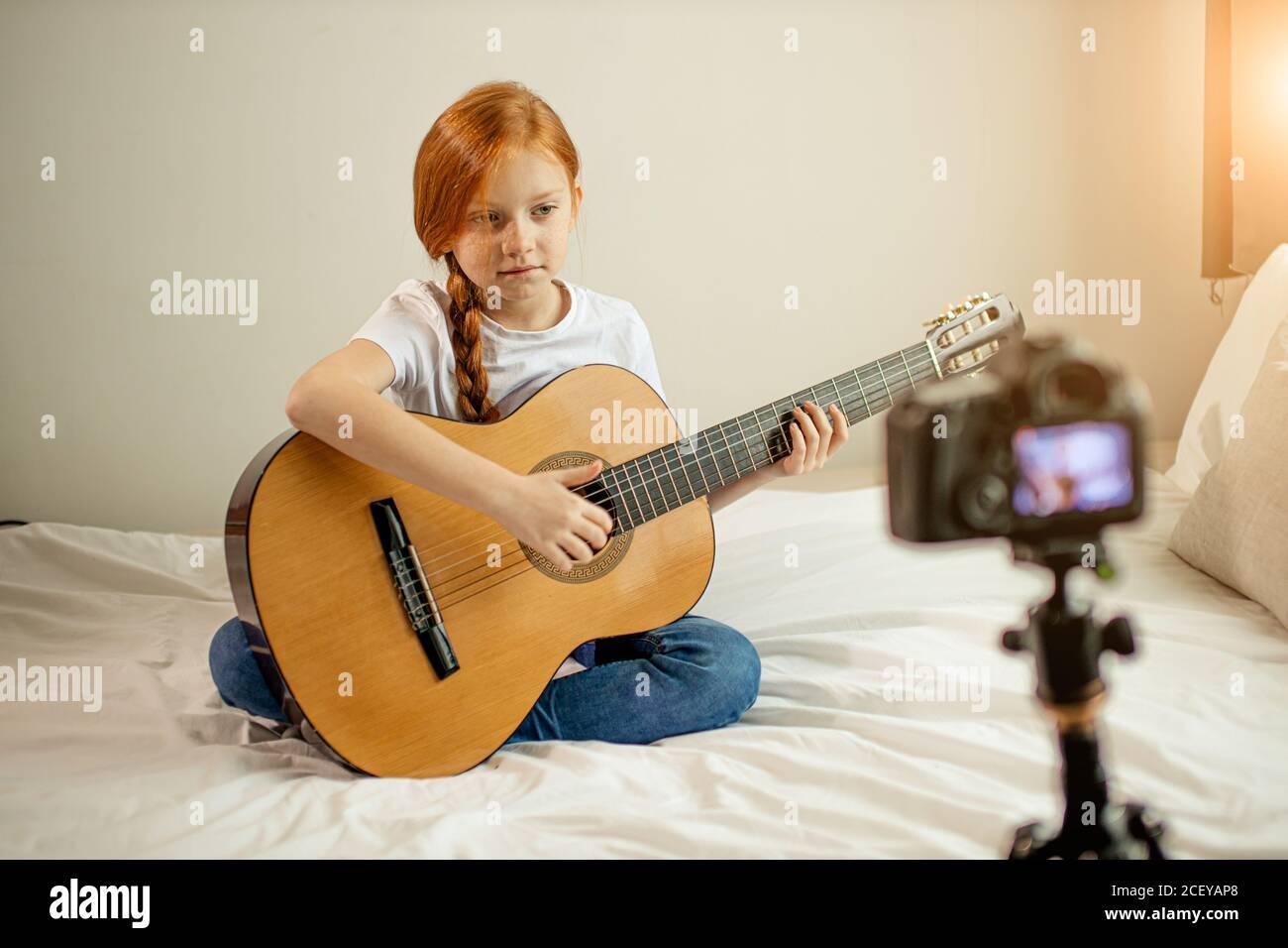 Portrait von schönen niedlichen kaukasischen Kind Mädchen blogger Gitarre spielen bei der Kamera. Liebenswert Mädchen sitzen zeigen, Durchführung neuer Melodie für Abonnenten. vl Stockfoto