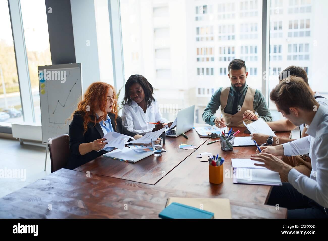 Internationale Gruppe von Menschen, Business-Team am Tisch versammelt, um Geschäftsideen zu diskutieren, mit Papieren, Diagramme. Kreative Geschäftsleute Stockfoto