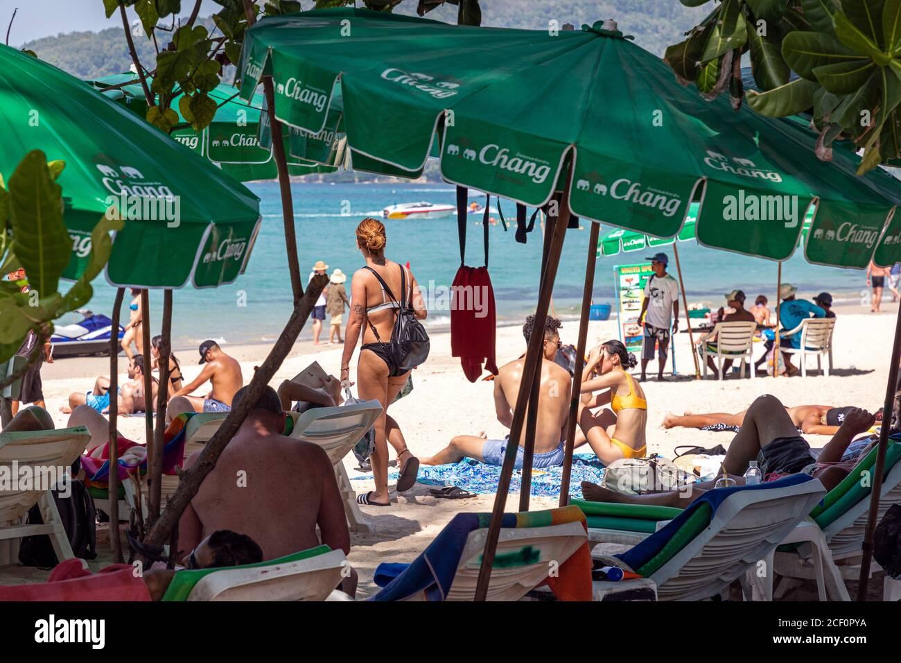 Tourist im Schatten unter Sonnenschirmen, Patong, Phuket, Thailand Stockfoto