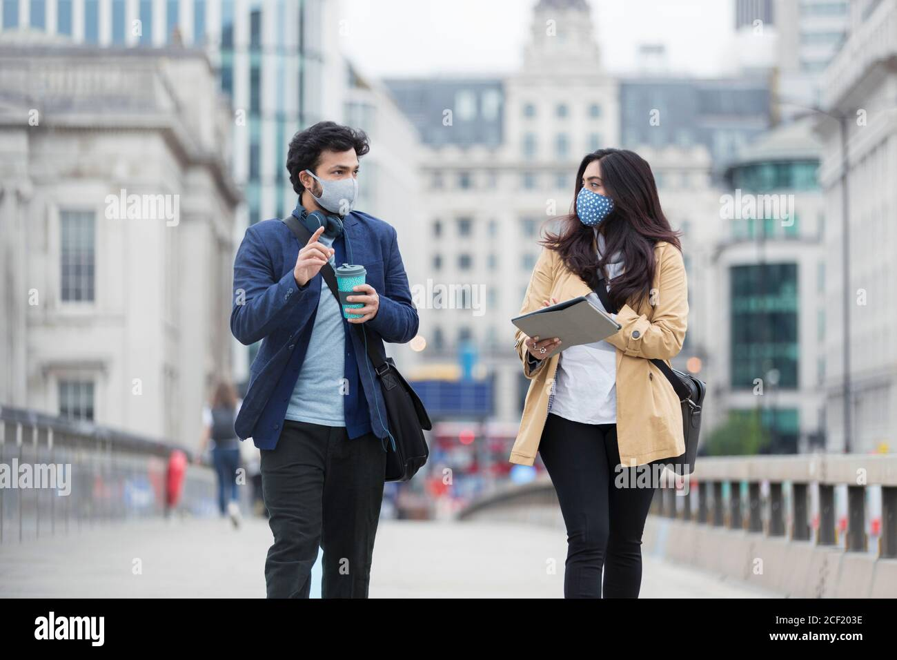 Geschäftsleute in Gesichtsmasken sprechen auf städtischen Fußgängerbrücke Stockfoto