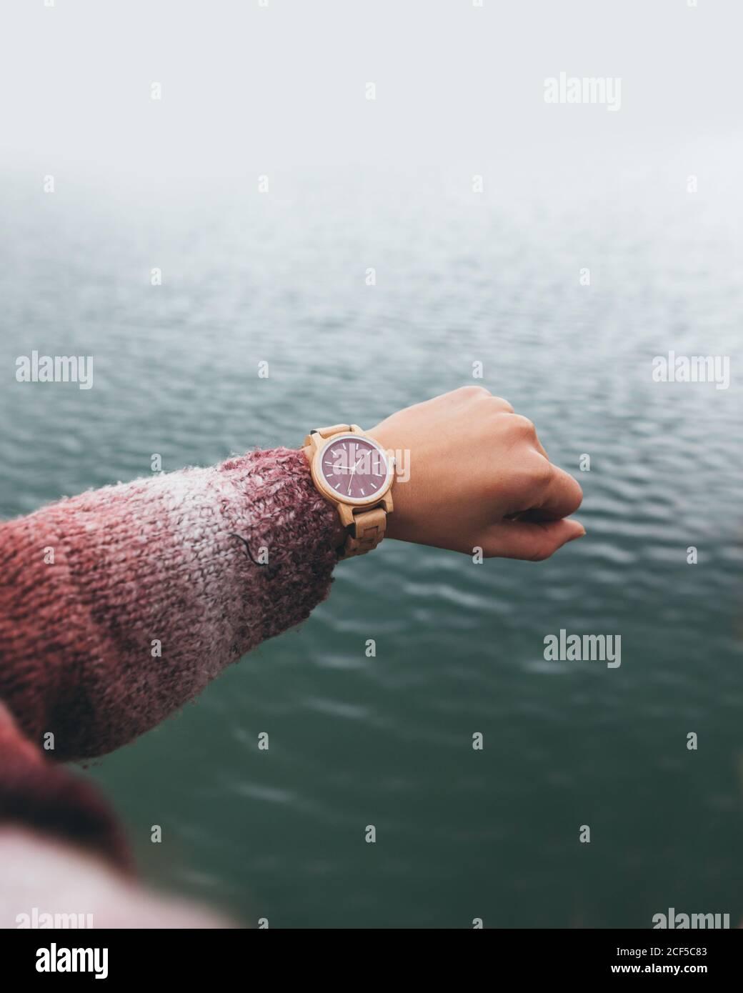 Von oben Ernte anonyme Frau in warmen Pullover Kontrollzeit Auf einer stilvollen Armbanduhr, während Sie die Hand über dem Fluss halten Tag Stockfoto