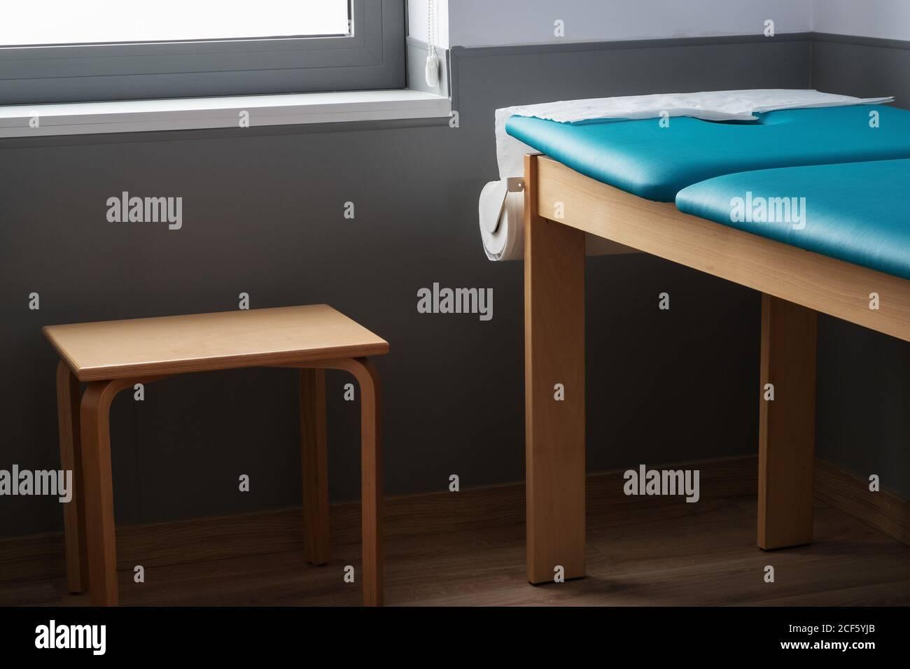 Leere Massageliege und Holzhocker im stilvollen Büro von Moderne Rehabilitationsklinik Stockfoto