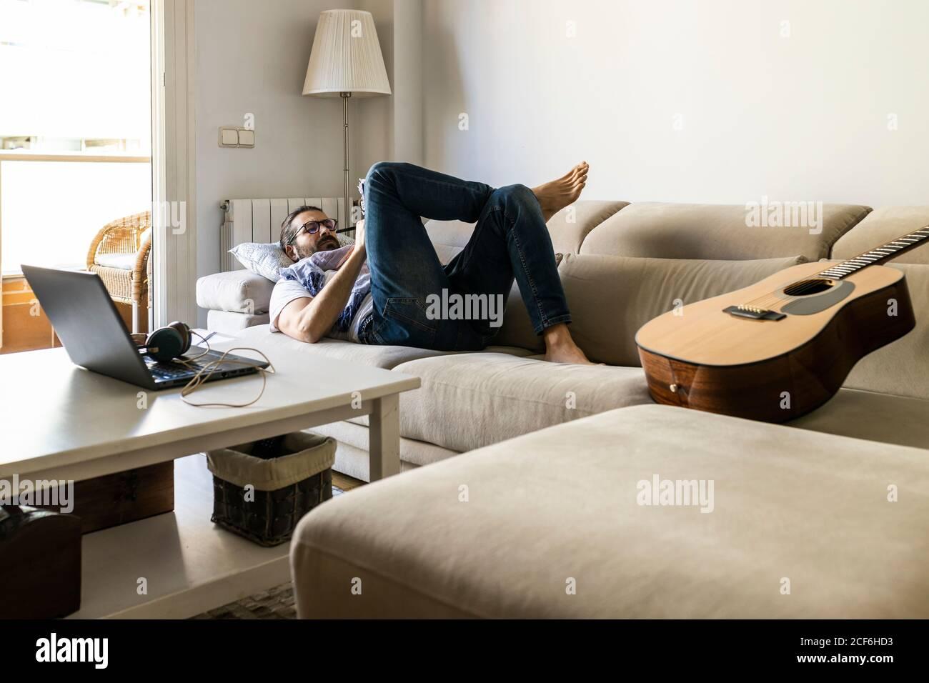 Mann schreibt Notizen auf der Couch im gemütlichen Wohnzimmer Stockfoto