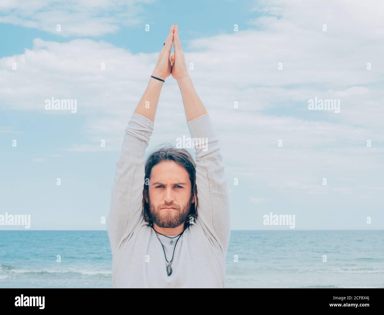 Sportlicher bärtiger Mann trainiert an ruhiger Küste und macht Yoga Asana gegen blaues Meer und Himmel Stockfoto