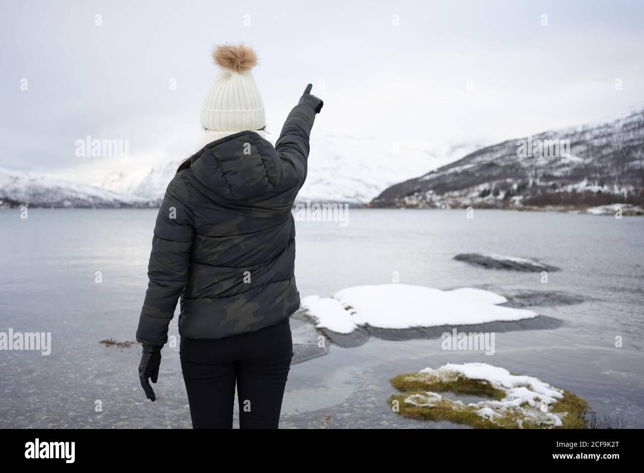 Rückansicht der anonymen Frau in warm Daunenjacke und hut zeigt mit dem Finger, während er am Strand gegen Weiß steht Und braune verschneite Hügel und ruhiges kühles Wasser des Kaldfjords see in Norwegen Stockfoto