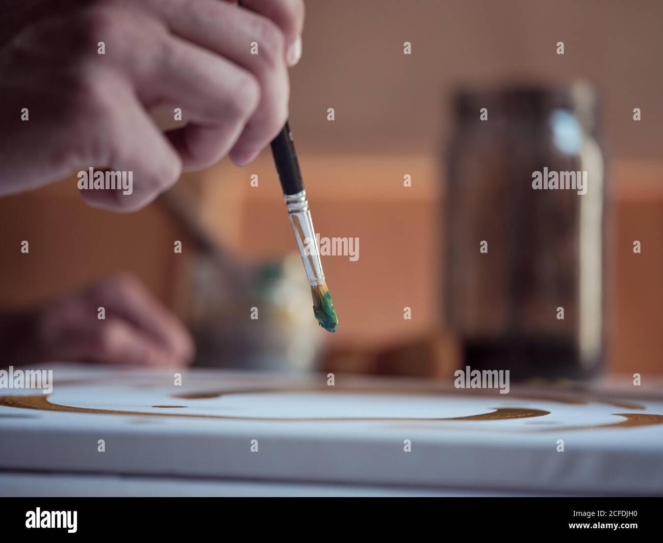 Nahaufnahme Hand des anonymen Künstlers mit Pinsel und grüne Farbe Zum Zeichnen von Bildern auf Leinwand im Studio Stockfoto