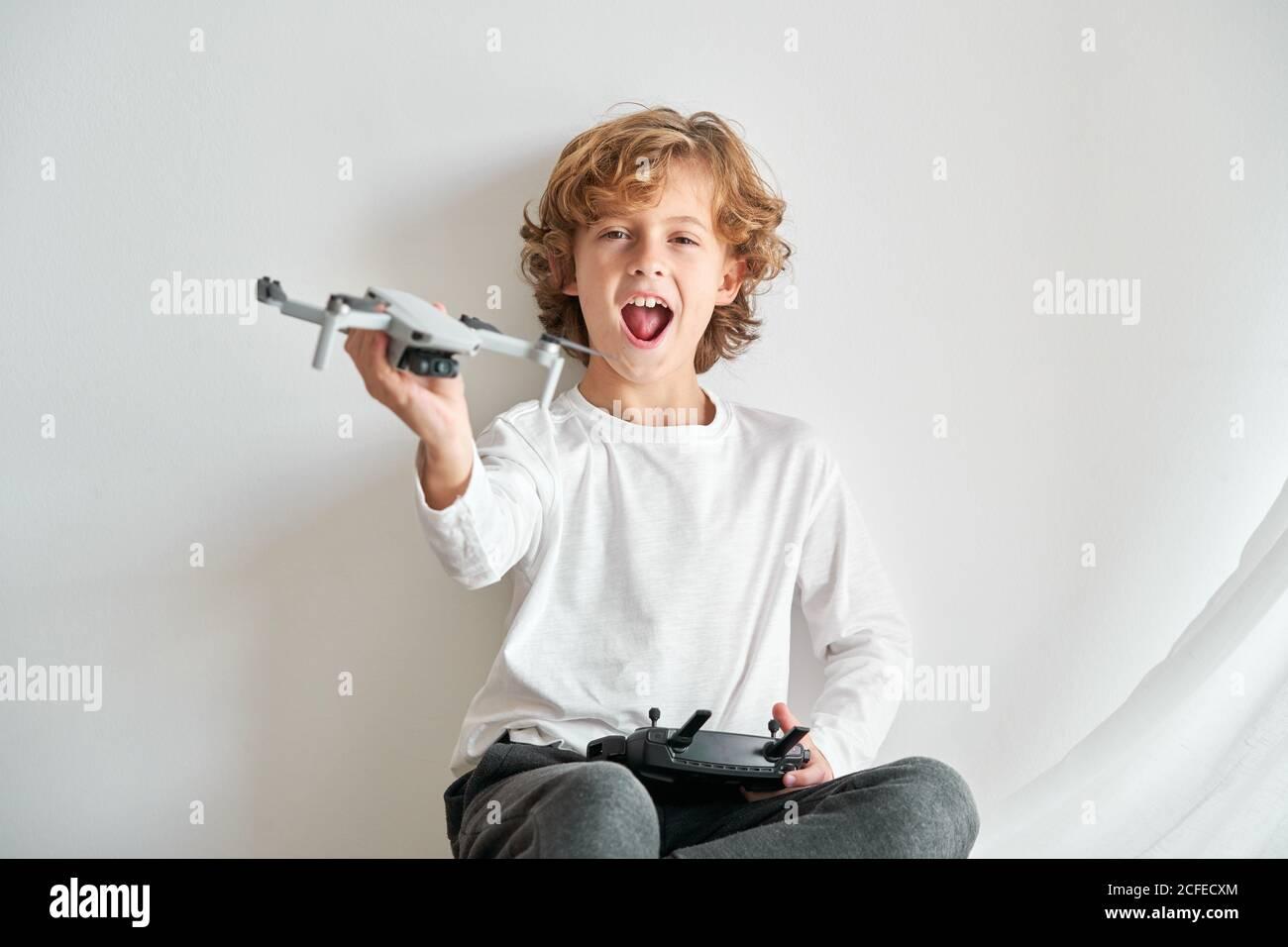 Kind manipuliert eine Drohne und die Fernbedienung gerade gegeben Zu ihm Stockfoto