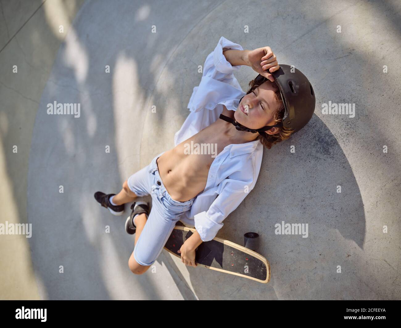 Blick von oben auf Kind im Helm liegend mit Augen geschlossen und chillen auf dem Boden im Skatepark mit Schatten Stockfoto