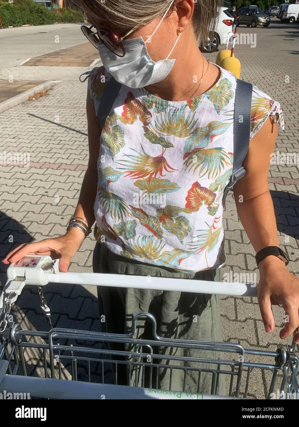 Covid-19. Frau trägt schützende Gesichtsmaske unter Warenkorb im Supermarkt. Stockfoto