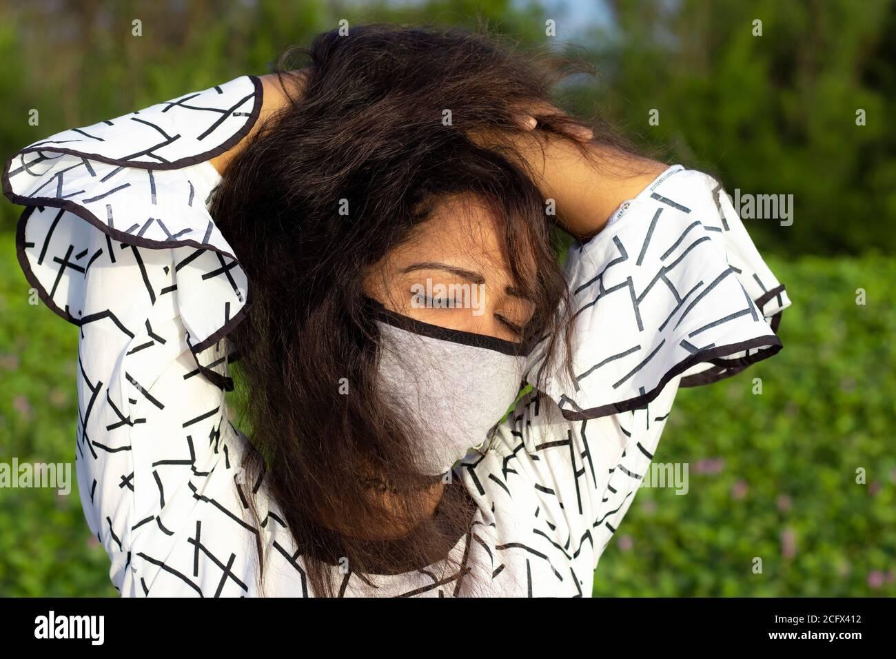 Stilvolle Frau trägt schützende Gesichtsmaske und posiert im Freien natürlichen grünen Hintergrund. Stockfoto