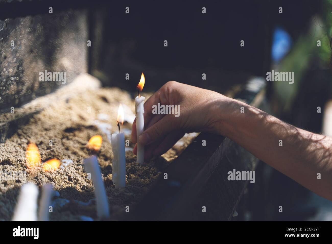 Frau, die im Garten des Hauses der Jungfrau Maria betet und Kerzen brennt. Brennende weiße Kerzen auf dem Stand. Anbetung Stockfoto