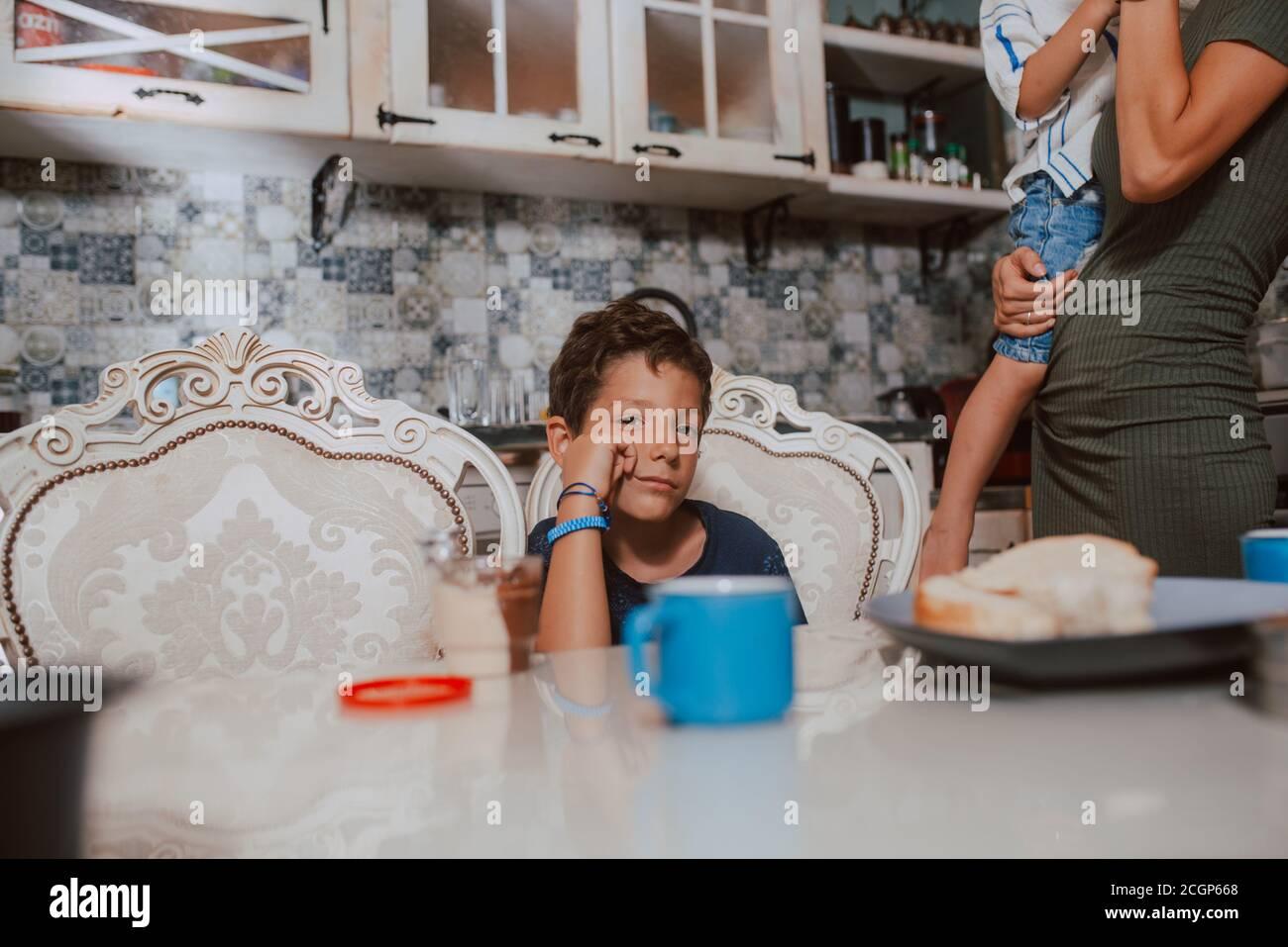 Eine schöne kaukasische Mutter in einem Kleid mit ihren beiden Söhnen steht während des Frühstücks in der Küche. Zeit mit der Familie Stockfoto