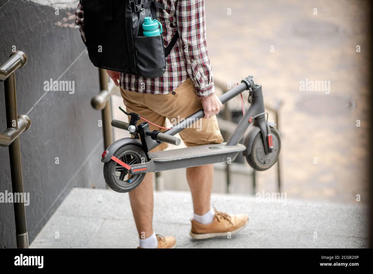 Der junge Kaukasusmann in legerer Kleidung mit Rucksack trägt einen gefalteten Elektroroller in der Hand die Treppe eines Bürogebäudes hinauf. Mann Trägt Stockfoto