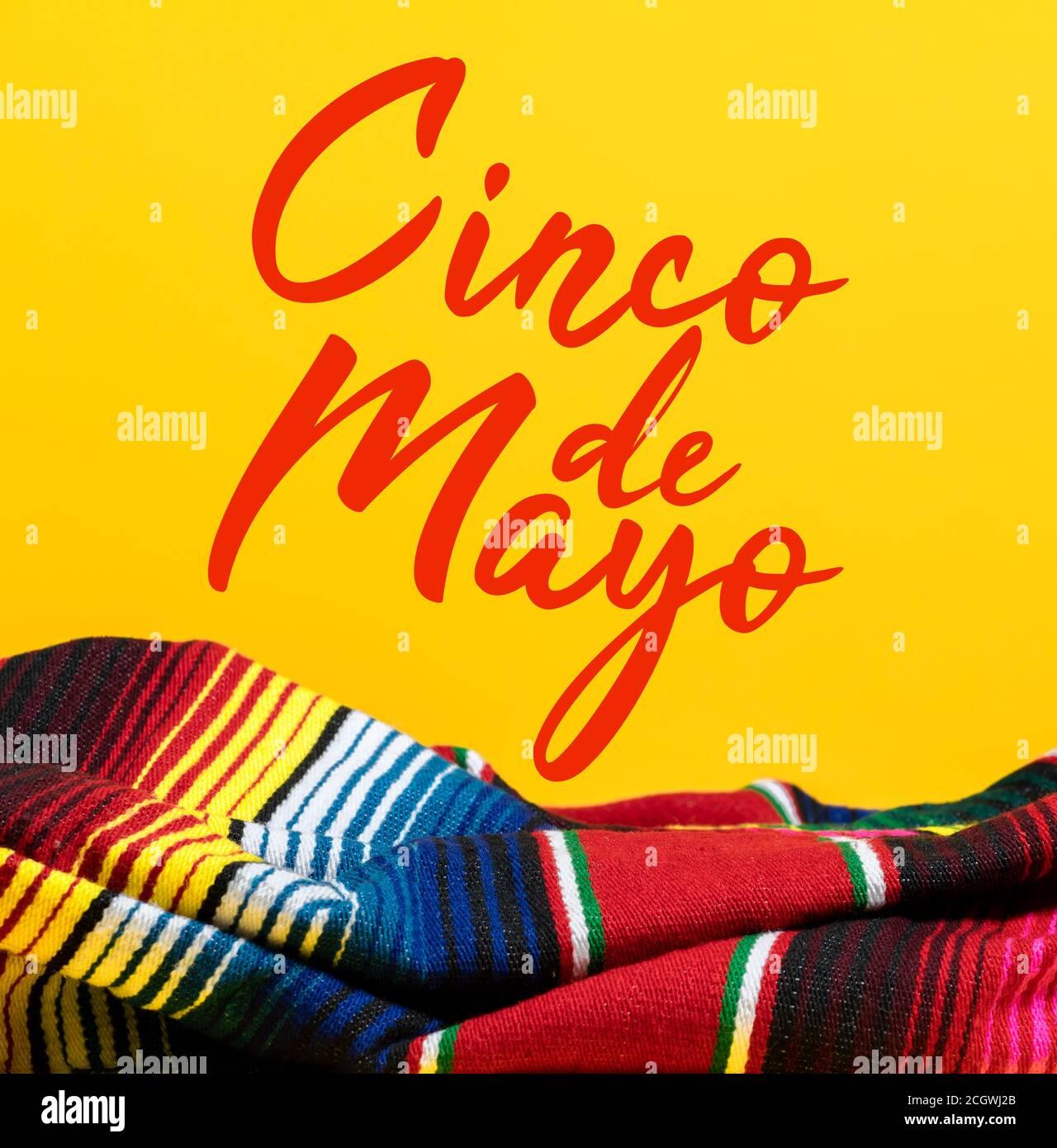 Mexikanische Serape Decke auf gelbem Hintergrund mit Cinco de Mayo. Stockfoto