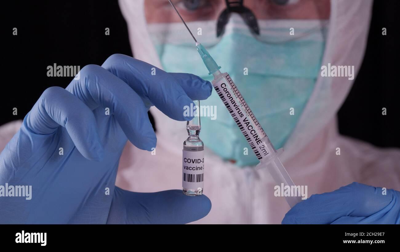 Coronavirus-Impfstoff. Mann in weißer Sicherheitsuniform, Maske und Brille mit Coronavirus-Impfstoffampulle und Spritze. COVID-19 Pandemieheilungskonzept Stockfoto