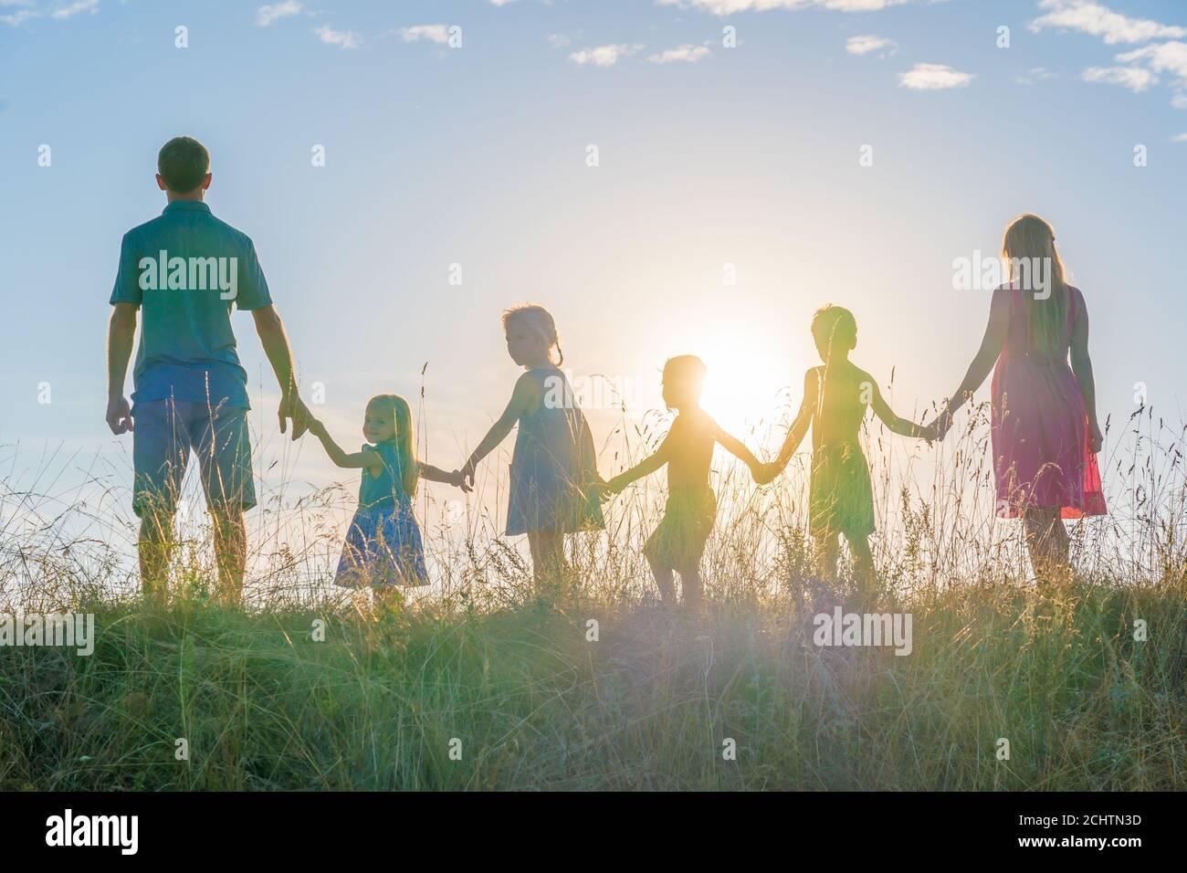 Eine große Familie steht mit Händen vor dem Hintergrund des Sonnenuntergangs. Stockfoto