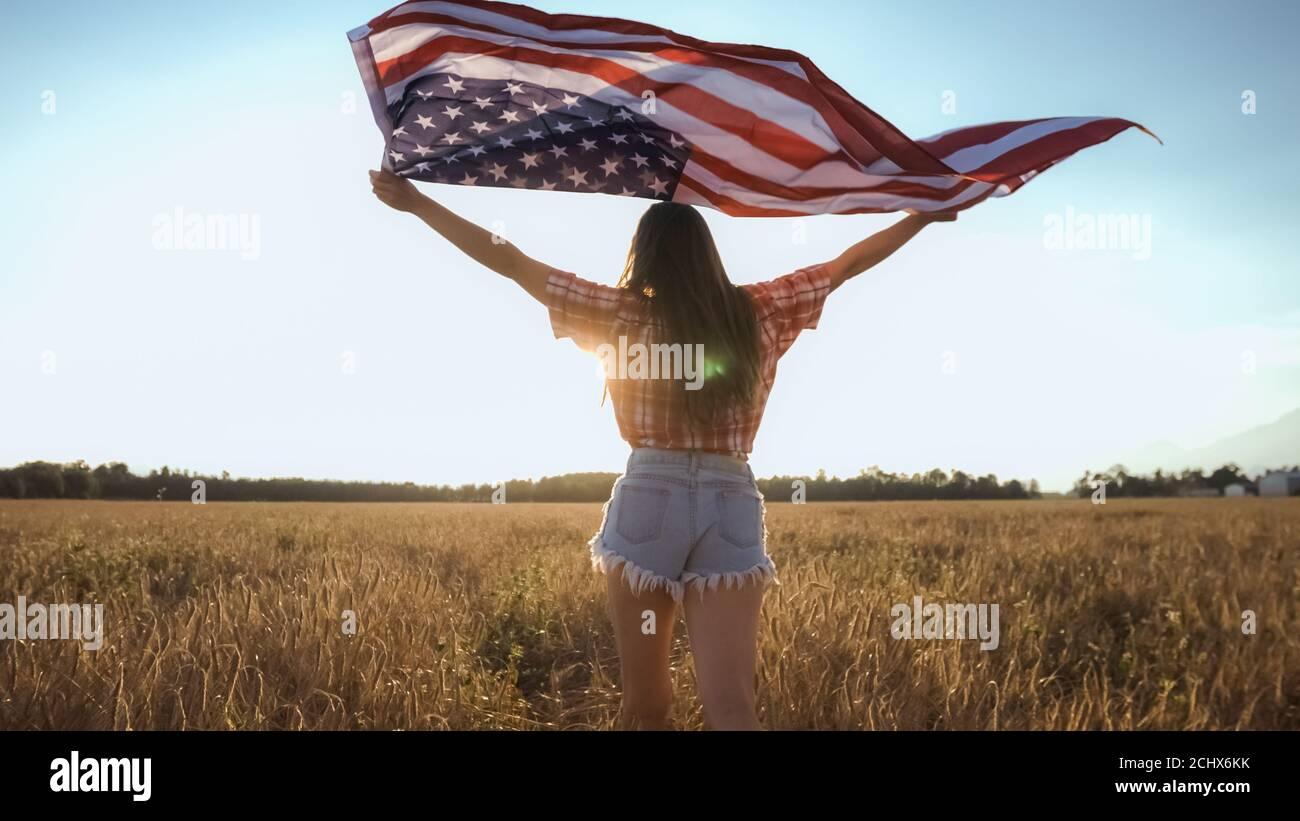 Junge glückliche amerikanische Mädchen laufen und springen am 4. Juli sorglos mit offenen Armen über Weizenfeld. Halten der Flagge der USA. Stockfoto