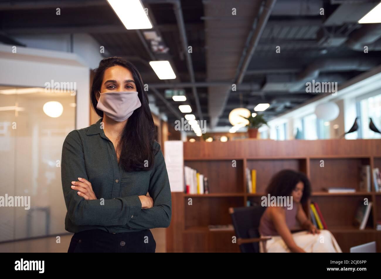 Porträt Der Geschäftsfrau Trägt Gesichtsmaske In Modernen Offenen Plan Büro Während Der Covid-19 Pandemie Stockfoto