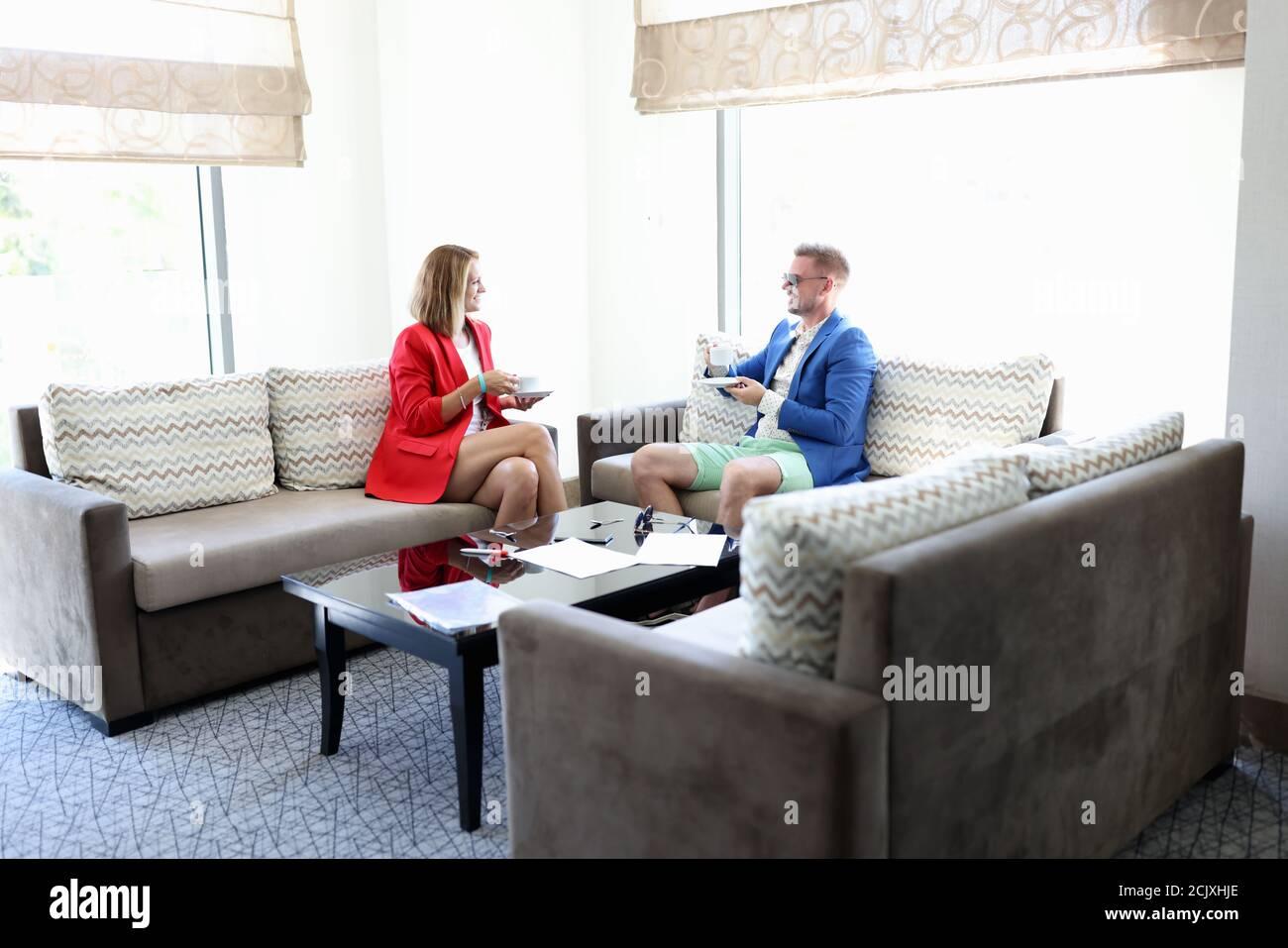 Junge Mann und Frau in modischer Kleidung mit Tassen Tee im Hotelzimmer Stockfoto