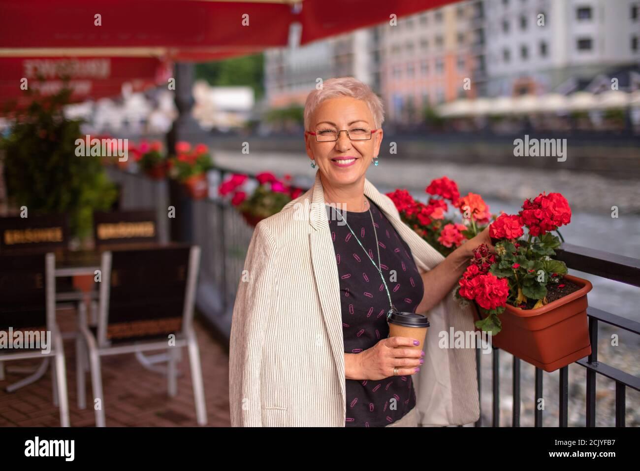Glückliche Frau mit wunderbaren Blumen auf dem Topf