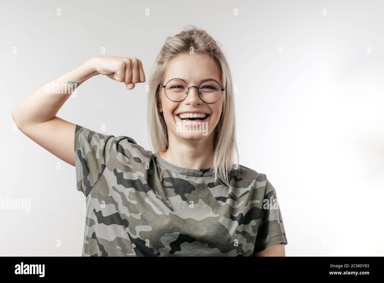 Schönes Mädchen in orange Tanktop und Jeans Shorts biegen Bizeps und Blick in die Kamera Lächeln. Drei Viertel Länge Studio auf lila Hintergrund gedreht Stockfoto