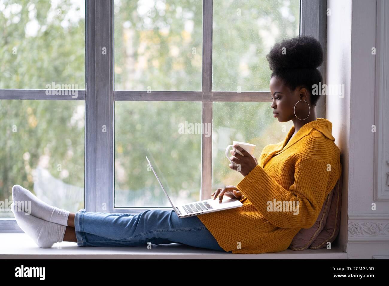 Fokussierte afroamerikanische Studentin mit Afro-Frisur tragen gelbe Strickjacke, sitzen auf Fensterbank, arbeiten Remote-Job auf Laptop, Vorbereitung Stockfoto