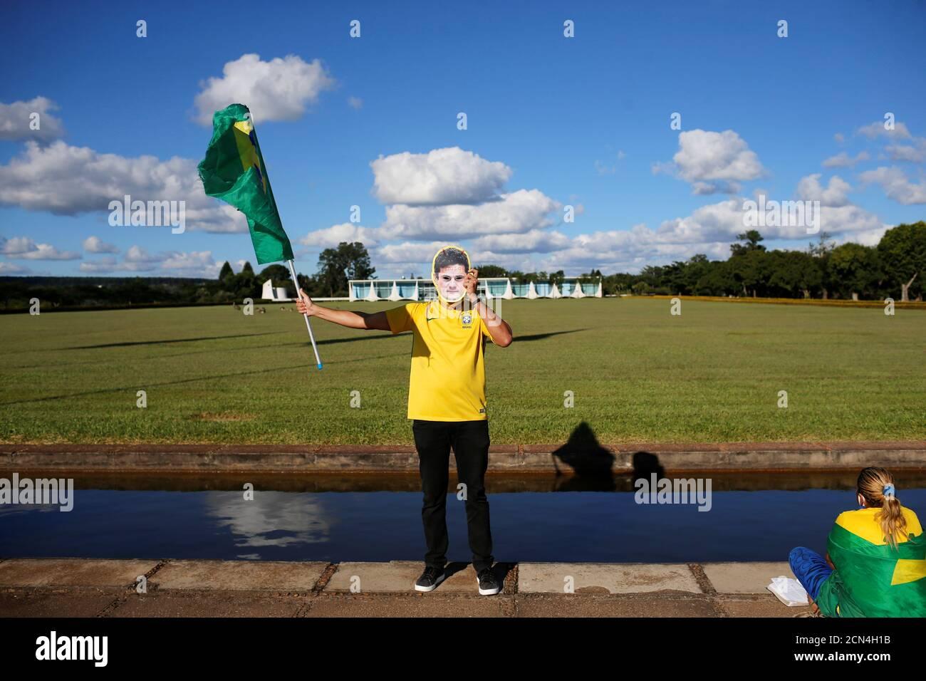 """Ein Anhänger des brasilianischen Präsidenten Jair Bolsonaro trägt eine Maske mit der Aufschrift """"Verräter"""" mit dem Bild des ehemaligen brasilianischen Justizministers Sergio Moro vor dem Palast Alvorada, inmitten des Ausbruchs der Coronavirus-Krankheit (COVID-19), in Brasilia, Brasilien, 26. April 2020. REUTERS/Adriano Machado Stockfoto"""