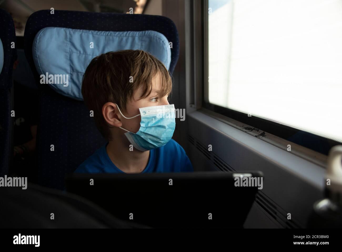 Boy sitzt in einem Zug mit Maske, Atemschutzmaske, medizinischer Maske, Mund- und Nasenschutz Stockfoto