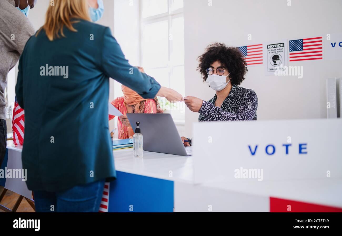 Menschen mit Gesichtsmaske Abstimmung in Wahllokalen, usa-Wahlen und Coronavirus. Stockfoto