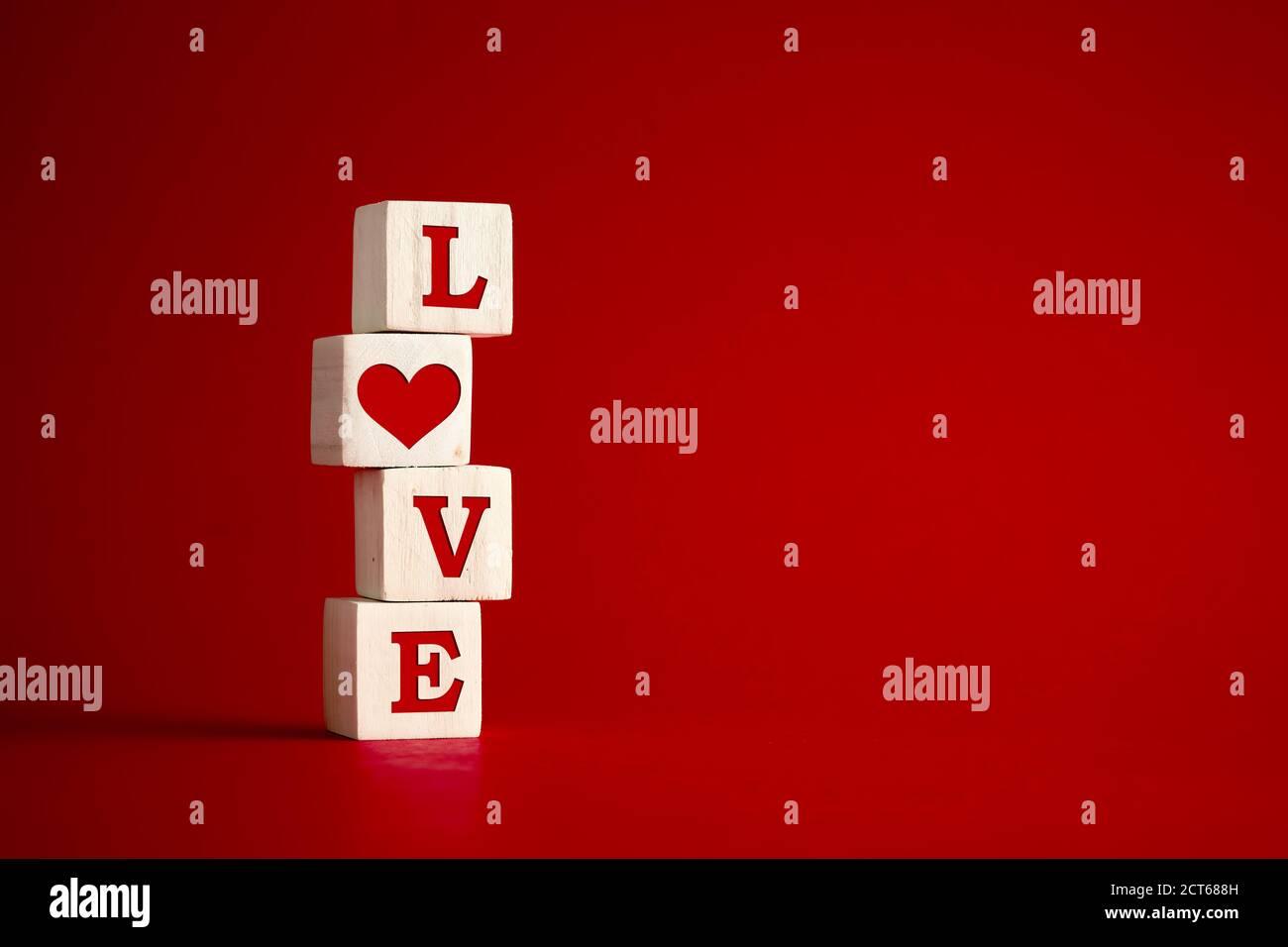 Das Wort Liebe mit Herzform auf Holzwürfeln vor rotem Hintergrund. Liebe, Romantik, Beziehung oder Valentinstag Konzept. Stockfoto