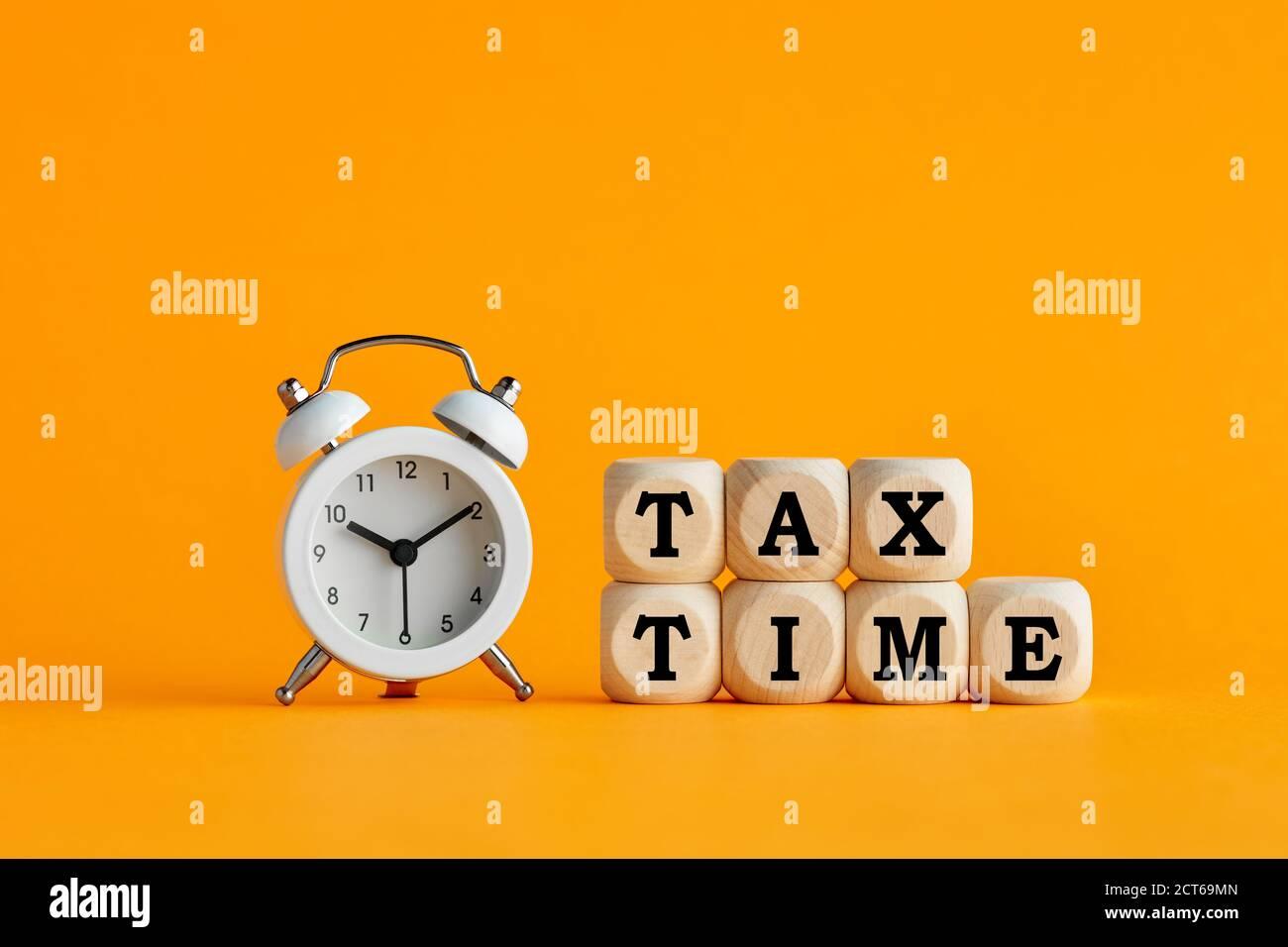 Das Wort Steuerzeit auf Holzwürfel mit Wecker auf gelbem Hintergrund geschrieben. Steuererinnerung oder jährliches Steuerkonzept. Stockfoto