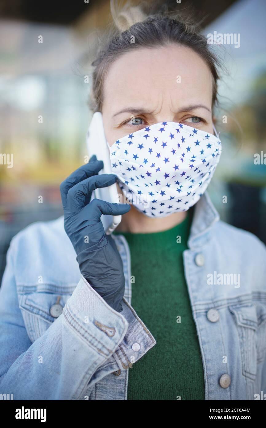 Junge hübsche Frau mit Nasen und Mundmaske im Gespräch Smartphone Stockfoto