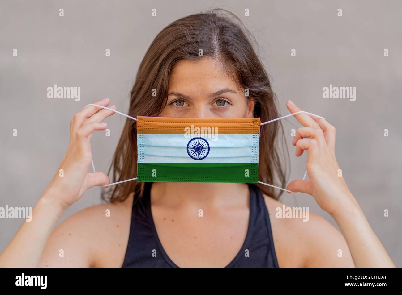 Ausbruch des Coronavirus in Indien und weltweite Gesundheitskrise. Frau trägt indische Flagge Gesichtsmaske gegen Infektionskrankheiten 2019 neuartige Coronavirus. Kontra Stockfoto