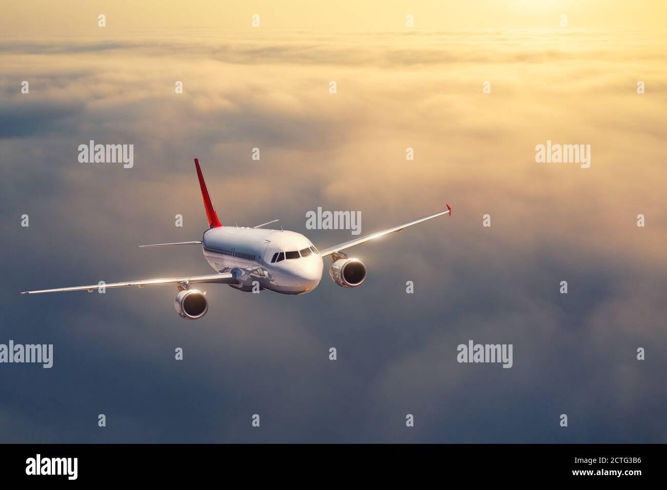 Das Flugzeug fliegt im Sommer bei Sonnenuntergang über den Wolken Stockfoto