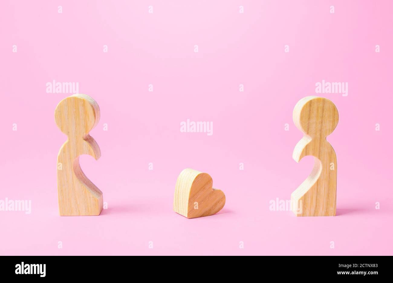 Figuren von Menschen getrennt voneinander und ein verlorenes Herz. Trennung, Ende der Liebe. Beziehungsprobleme des Paares. Machen Sie den ersten Schritt in Richtung Stockfoto