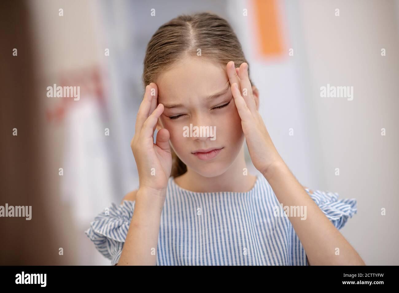 Mädchen mit Kopfschmerzen und unglücklich aussehen Stockfoto