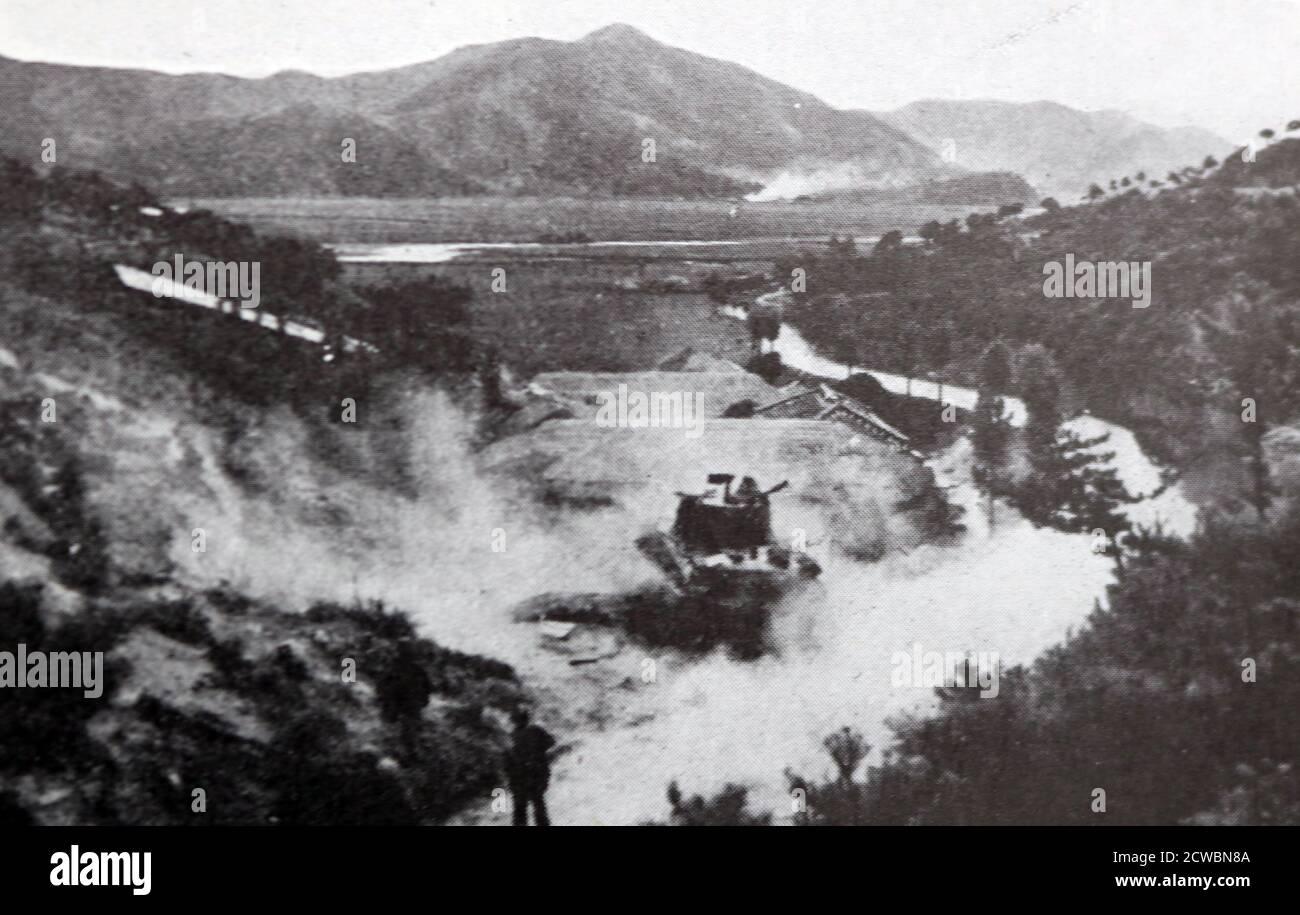 Schwarz-Weiß-Fotografie des Koreakrieges (1950-1953); amerikanische Infanteristen, die unter dem Schutz eines Panzers vorrücken, der das Feuer auf ein vom Feind besetztes Dorf eröffnet. Stockfoto