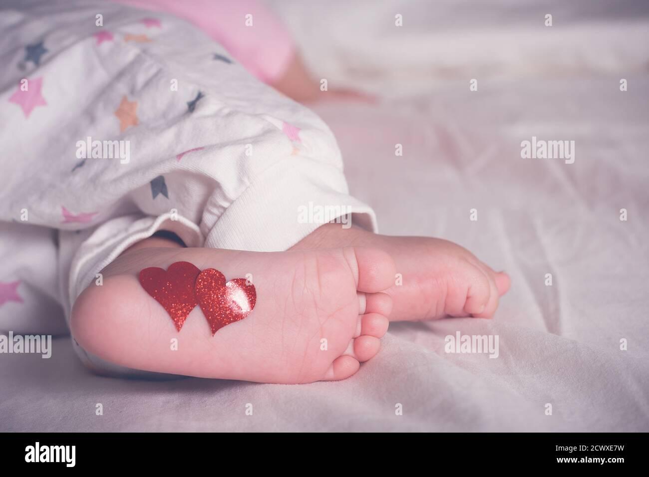 Babynasse mit Herzen auf den Füßen. Ein neugeborenes Baby liegt auf dem Bett. Stockfoto