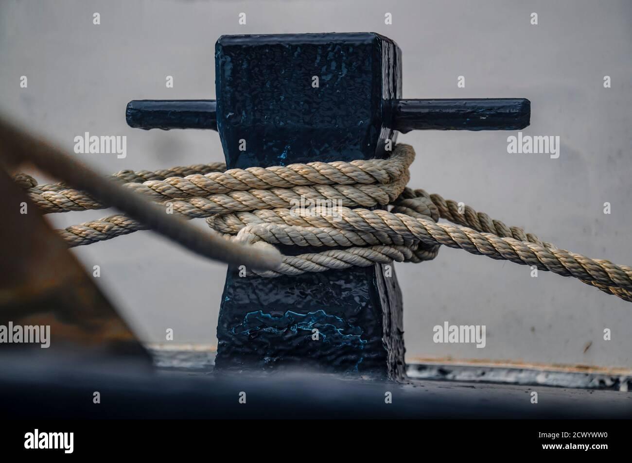 Nahaufnahme des Bootes Poller mit einem Seil um ihn gebunden. Verbindung visuelles Konzept als Boot gebunden und mit dem Ponton verbunden. Stockfoto