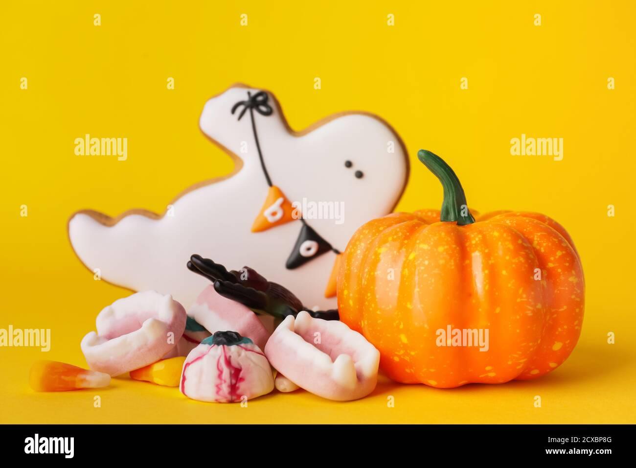 Leckere Leckereien für Halloween auf farbigem Hintergrund Stockfoto