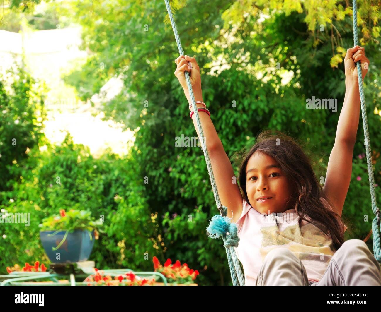 Junge lächelnde Mixed-Race-Mädchen schwingt in einem Park während der Urlaub Stockfoto