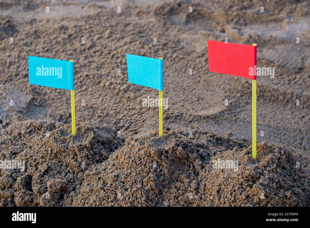 Im Sandkasten drei Sandhügel von links nach rechts mit zwei blauen Fahnen auf der linken und roten Flagge auf der rechten Seite. Konzept: Führung in der Geschäftsstrategie Stockfoto
